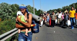 Un hombre sirio lleva a su bebé en brazos y se dirige hacia Viena, Austria. Foto: ACNUR/Mark Henley.