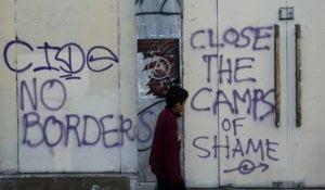 Un niño pasa delante de unas pintadas hechas en Atenas a mediados de abril durante una manifestación contra la guerra en Siria y la actitud de la UE hacia los refugiados. S. PANTZARTZI EFE