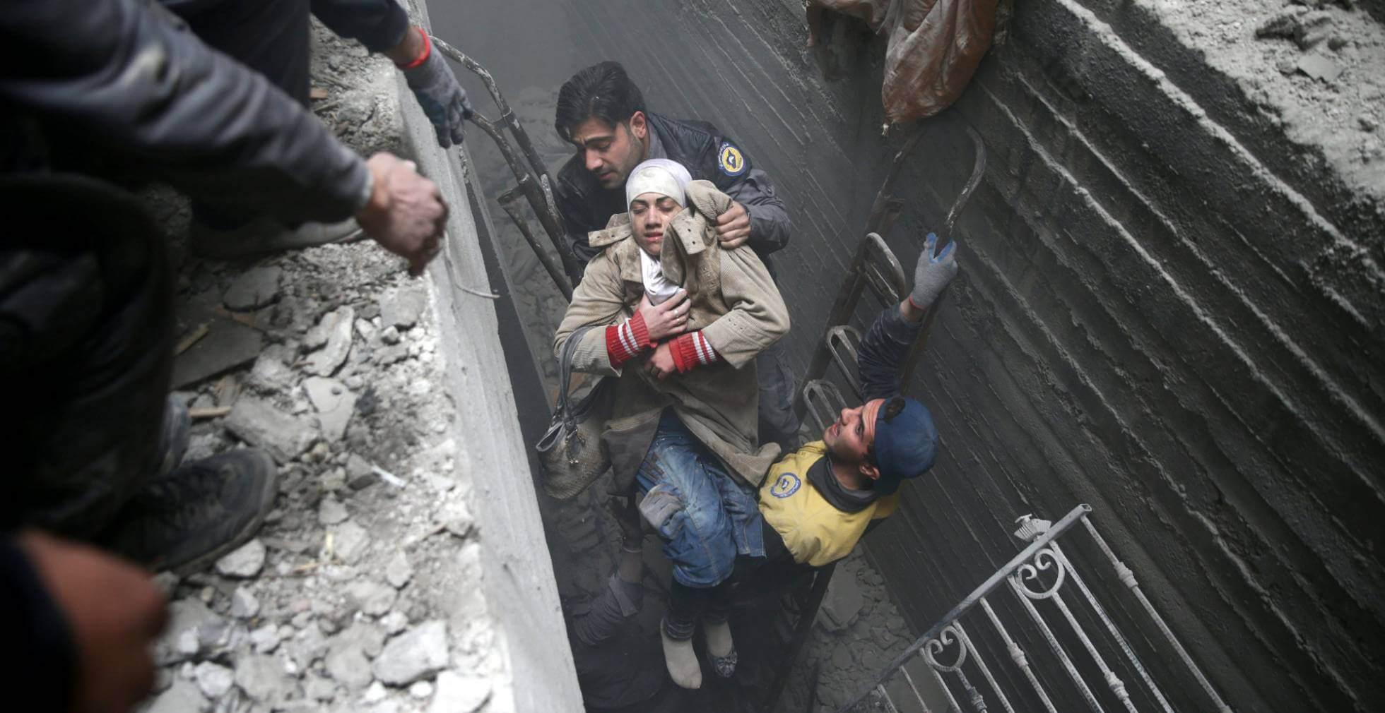 Miembros de la Defensa Civil Siria rescatan a una mujer tras un bombardeo en Duma. BASSAM KHABIEH REUTERS