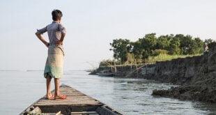 OIM/Amanda Nero Un niño observa la orilla desde un barco cerca de Sirajganj, una comunidad afectada por la grave sequía que ha dejado a muchos desplazados. Sirajganj, Bangladesh